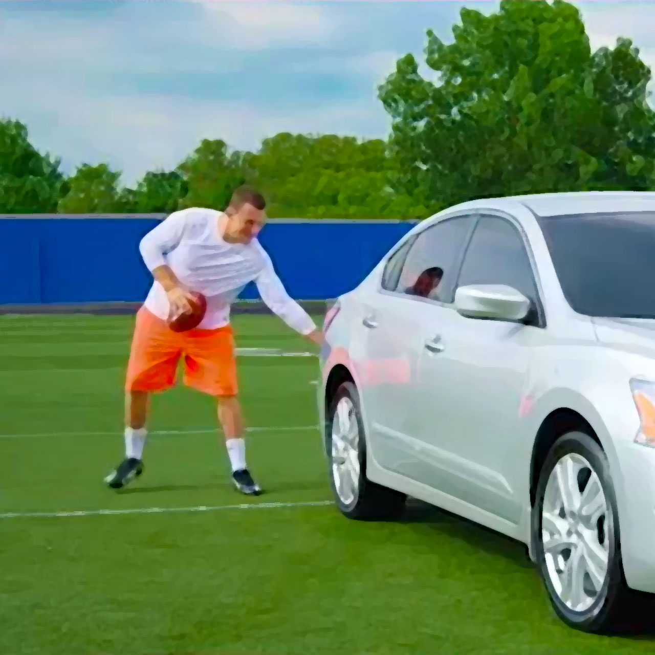 Johnny Manziel pats a Nissan Altima on the bumper