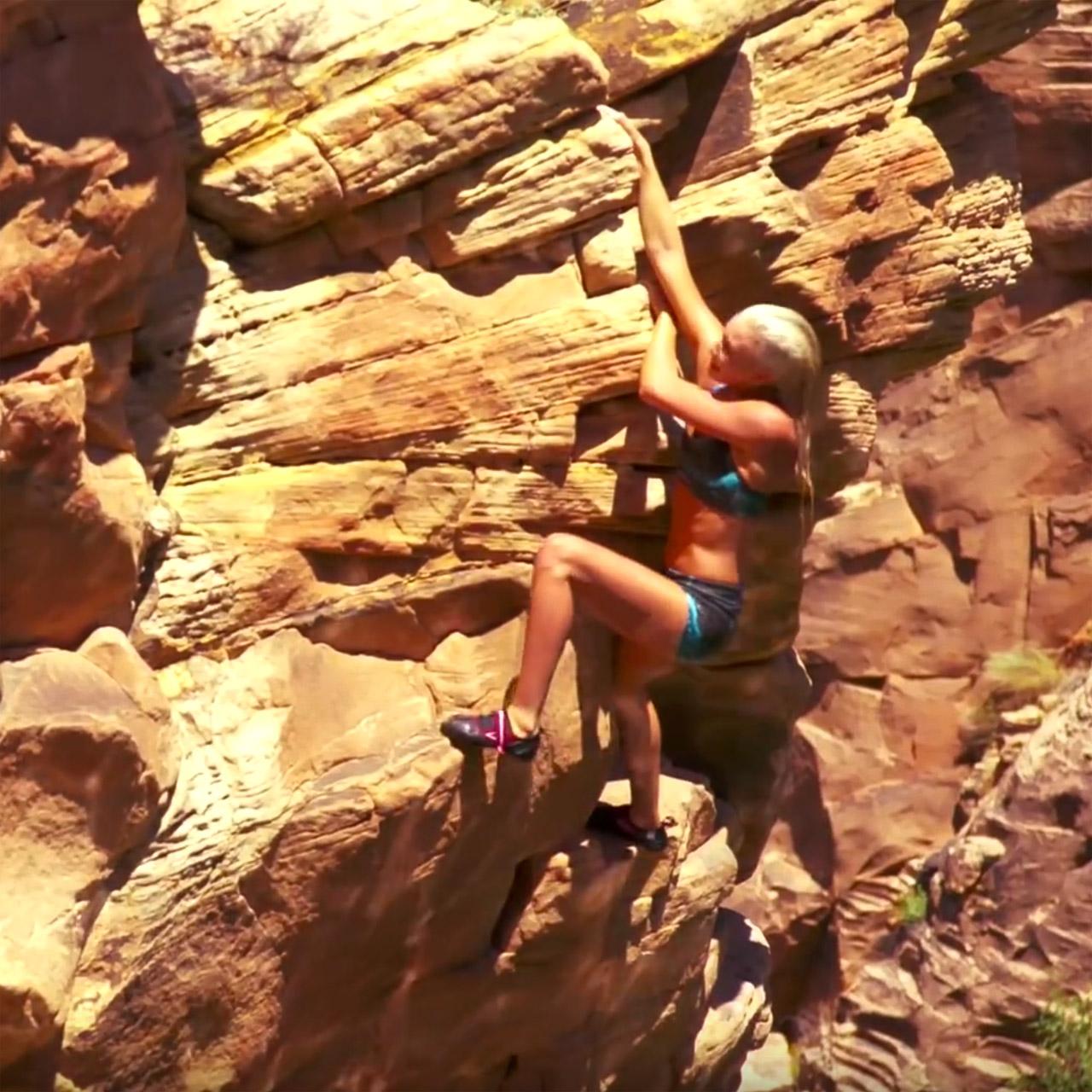 Sierra Blair-Coyle free climbing on riverside cliffs